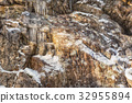 Many small icicles on a stone wall 32955894