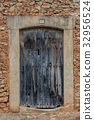 Old wooden door in brick wall 32956524