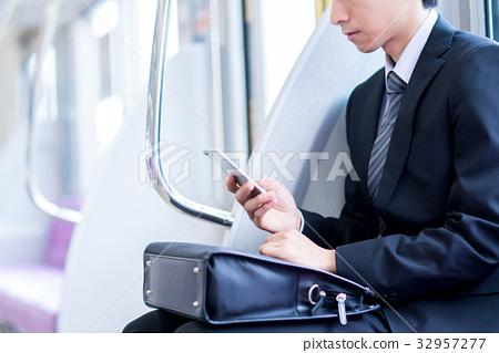 """在通勤列車""""京王電鐵株式會社""""上操作智能手機的商人 32957277"""
