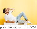 Handsome tanned man lying on white box 32962251