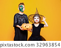 Kids in Halloween Costumes Playing with Pumpkin 32963854
