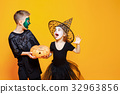 Kids in Halloween Costumes Playing with Pumpkin 32963856