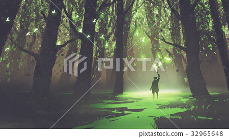 alone man with torch standing in fairy tale forest 32965648