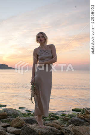 Beautiful young model in a long dress on the coast 32966053