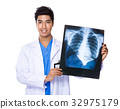 Young doctor holding with x ray film 32975179