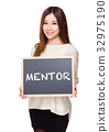 Woman hold with chalkboard showing a word mentor 32975190