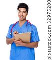 Male doctor take note on clipboard 32975200