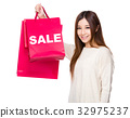 Young Woman hold with shopping bag showing a word sale 32975237