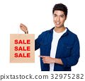 Man finger point to shopping bag for showing three sale words 32975282