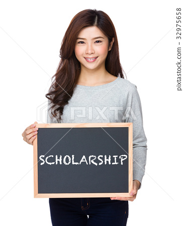 School girl hold with chalkboard and showing a word scholarship 32975658
