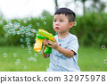 Little boy play with the bubble gun machine 32975978
