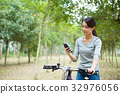 Woman checking the GPS on mobile phone when cycling 32976056