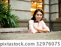 Woman relaxing at outdoor cafe 32976075