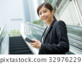 Businesswoman going up to escalator 32976229