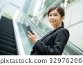 Asian Businesswoman holding a cellphone and standing on escalator 32976266