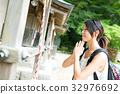 Woman wishing in Japanese temple 32976692