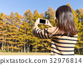 Woman taking photo by cellphone in autumn forest 32976814