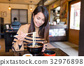 Young woman eating japanese udon in restaurant 32976898