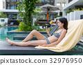 Woman relaxing in pool side with sunbathing 32976950