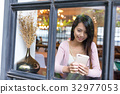 Woman use of mobile phone inside coffee shop 32977053