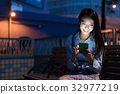 Woman using mobile phone at night 32977219