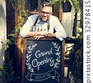 Man with grand opening blackboard in front the shop 32978415