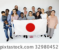 Group of people holding japanese flag studio portrait 32980452