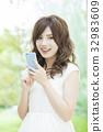 ผู้หญิงที่ดูสมาร์ทโฟน 32983609