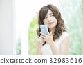 ผู้หญิงที่ดูสมาร์ทโฟน 32983616