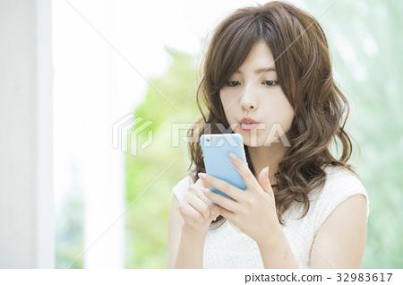 ผู้หญิงที่ดูสมาร์ทโฟน 32983617