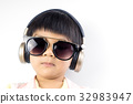 boy is listening to music with golden headphone 32983947