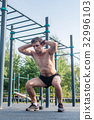 Muscular fitness athlete doing squats with his 32996103
