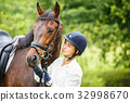 Young rider woman in helmet holding bay horse 32998670