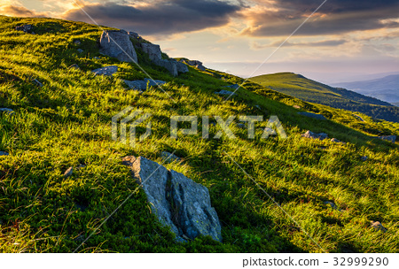 grassy meadow with boulders on mountain slope 32999290