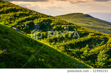 grassy meadow on mountain slope 32999291