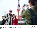 a girl is taking photo of couple near a tower 33006779