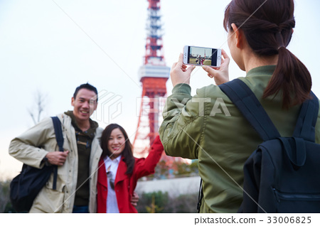 A girl is taking photos for a foreign couple near a tower 33006825