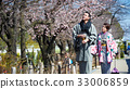 young couple in kimono is walking and looking at cherry blossom 33006859