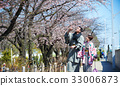 handsome man is pointing to cherry blossom for woman 33006873
