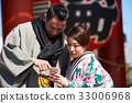 The portrait of man and woman in kimono looking at smartphone 33006968