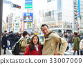 a couple is standing on the crowded street 33007069