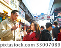 a photo of a couple eating outside the street 33007089