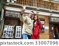 a photo of a couple standing outdoors and taking selfie 33007096