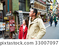 a couple is walking on a street and looking for something 33007097