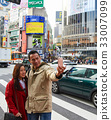 a picture of a couple standing on the street and taking selfie 33007099