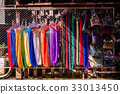 Colorful hammocks hanging on rack under sunlight. 33013450