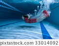 Swimmer in the dress dives underwater. 33014092