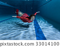 Swimmer underwater in the pool. 33014100