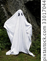 Ghost standing in front of a rock 33017044