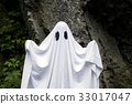 Ghost standing in front of a rock 33017047